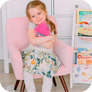Девочка с игрушкой на мягком стуле