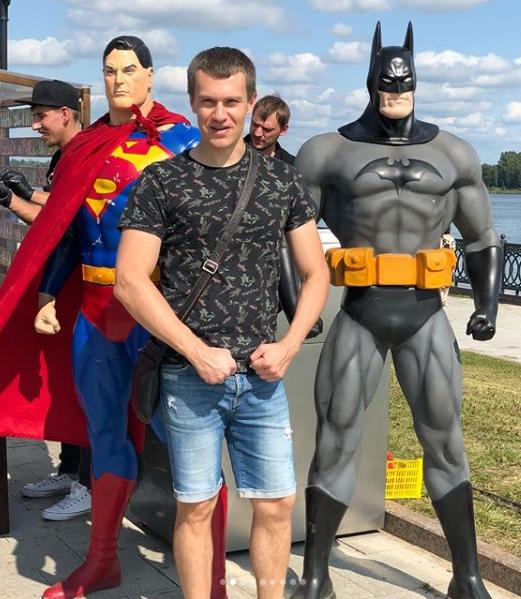 Мужчина на фоне супергероев.