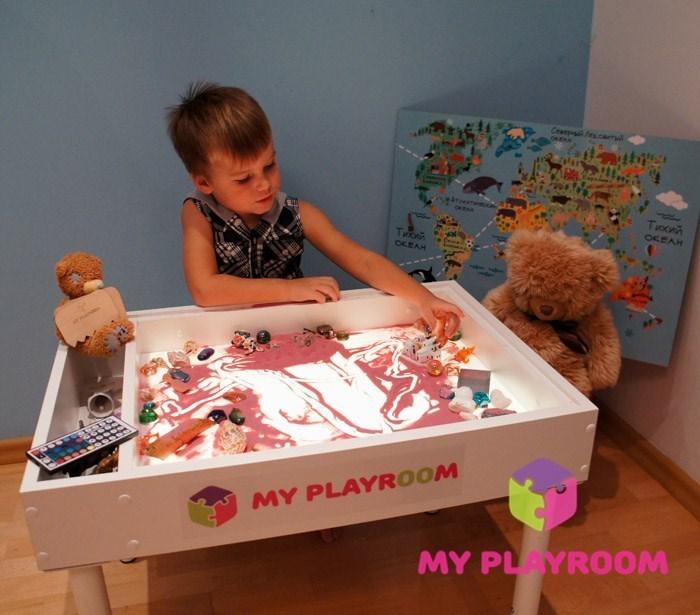Мальчик играет за световым столом Myplayroom