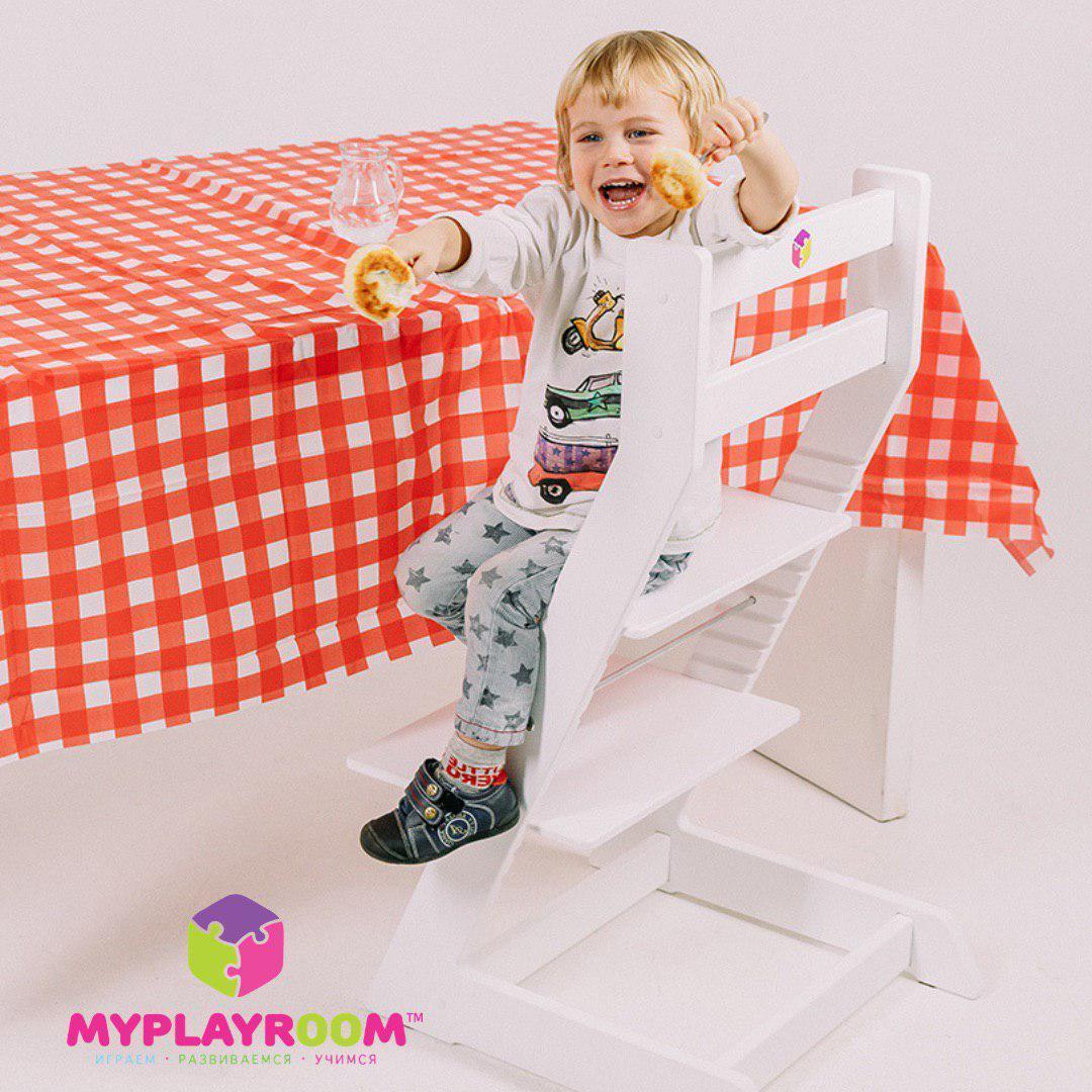 Самостоятельный малыш на растущем стуле за взрослым обеденным столом